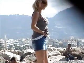 Gorgeous milf undressing on the beach